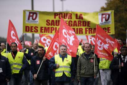 Employees of Air France wave CGT union flags (General Confederation of Labour), as they take part in a demonstration in front of the company headquarters, during the launch of the plan at a central committee meeting, in Roissy-en-France, on October 5, 2015. Air France-KLM unveiled a revamped restructuring plan on October 5 that could lead to 2,900 job losses after pilots for the struggling airline refused to accept a proposal to work longer hours. AFP PHOTO / KENZO TRIBOUILLARD